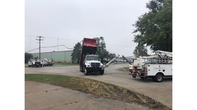 Dump truck hits utility pole, driver safely removed after bed gets entangled in wires